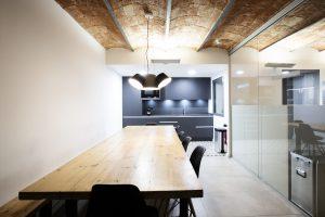 Cocina con gran mesa de unas oficinas reformadas